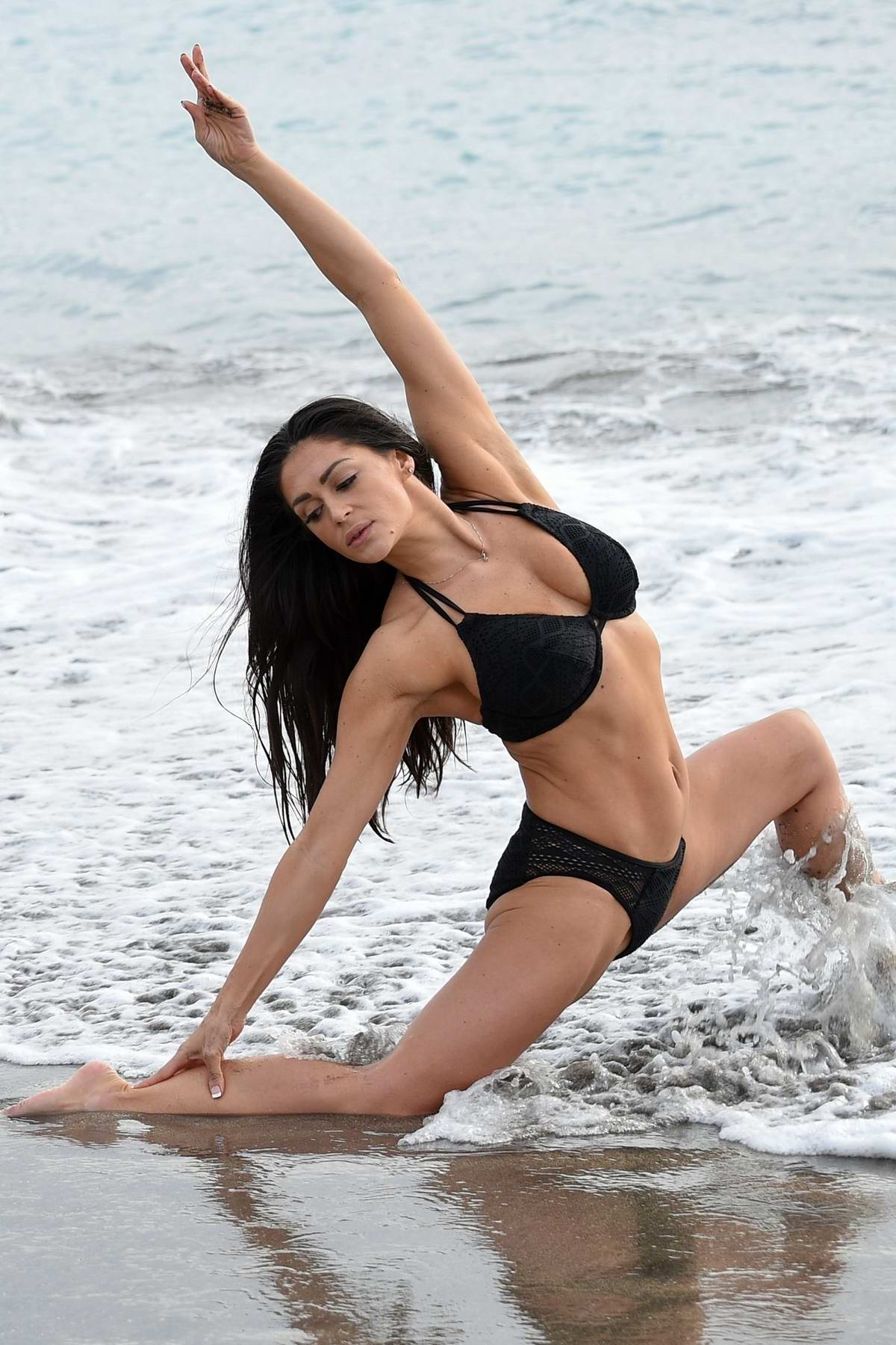 Casey Batchelor shows off her flexible physique in a black bikini while filming for her fitness app Yoga Blitz in in Tenerife, Spain