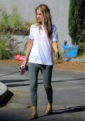 Chrishell Stause wears a white tee and grey leggings while out walking her dog in Los Angeles