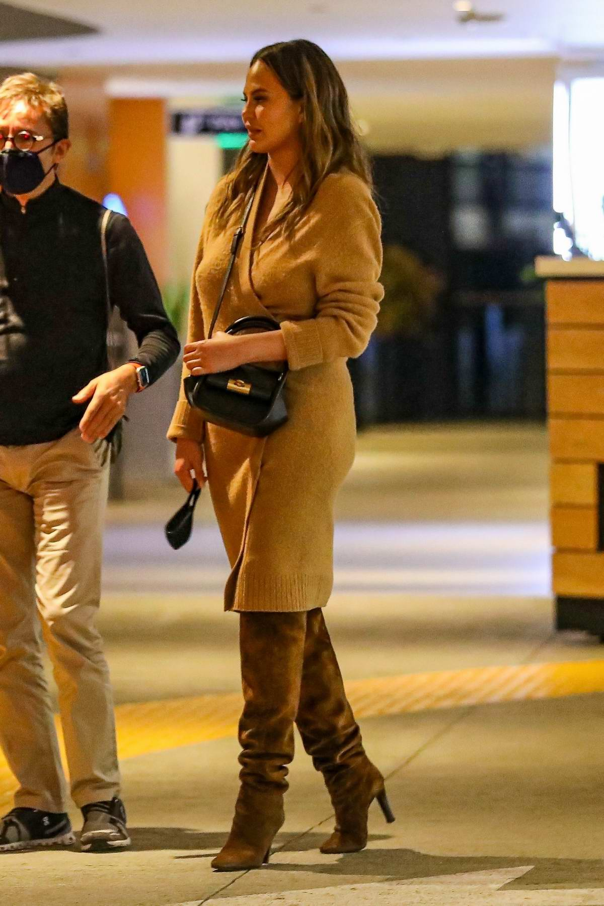 Chrissy Teigen looks stylish in a wrap dress and knee-high suede boots during a dinner outing in Los Angeles