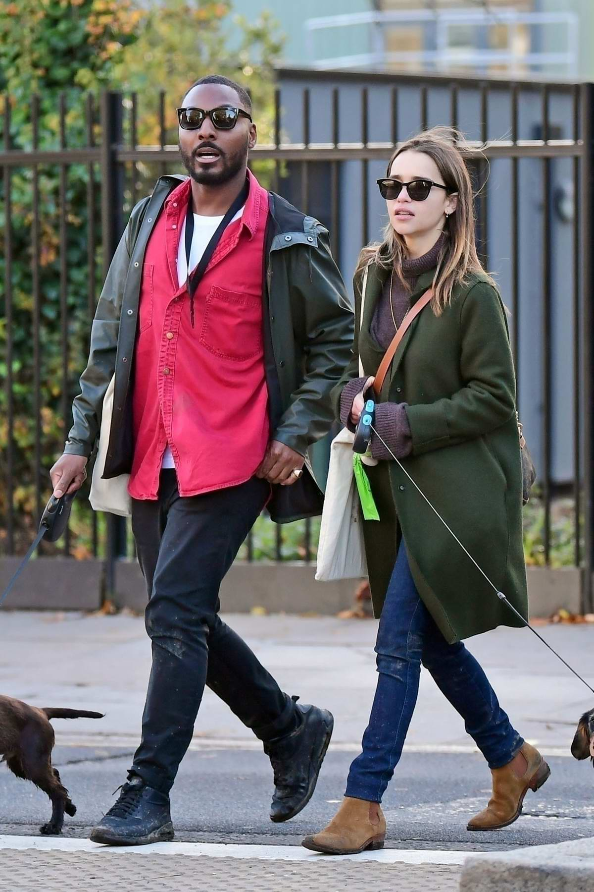 Emilia Clarke bundles up in a green coat and brown turtleneck while walking her dog with a friend in London, UK
