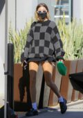 Hailey Bieber puts on a leggy display in denim shorts paired with a checkered sweater while out in West Hollywood, California
