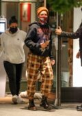 Halsey dresses down in plaid pants with a black hoodie and a beanie for dinner with friends in New York
