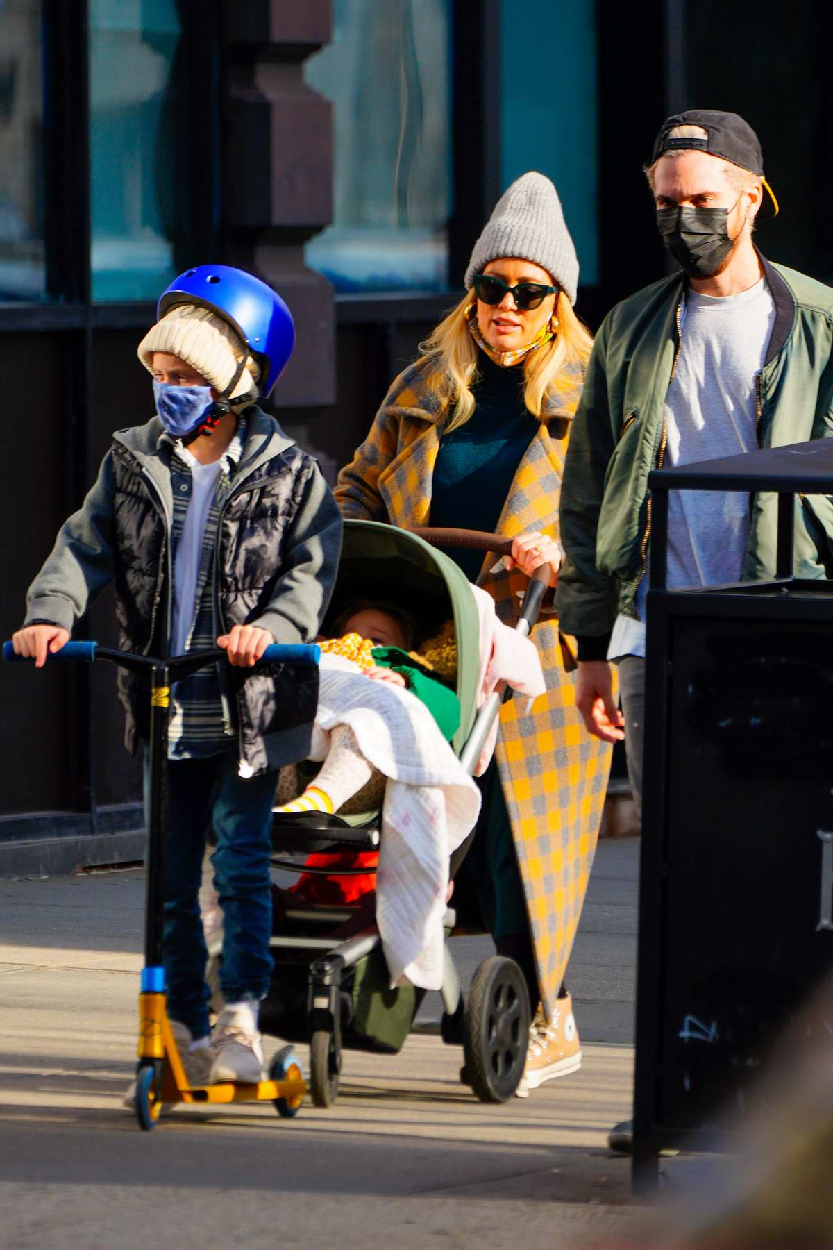 Hilary Duff bundles up in a warm checkered coat while out for a stroll with her family in New York City