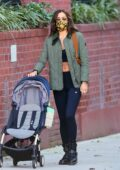 Irina Shayk flashes her midriff as she wears a black crop and leggings with a green jacket while running errands before picking up her daughter in New York