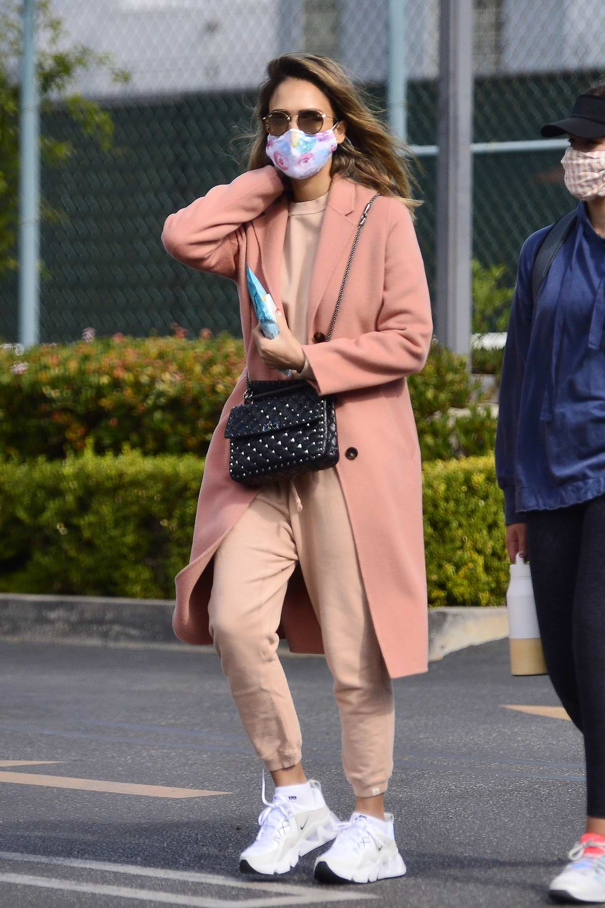 Jessica Alba seen wearing a peach pink overcoat with matching sweats as she leaves a tennis lesson in Los Angeles
