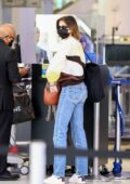 Kaia Gerber sports a yellow and brown sweater and jeans as she arrives for a flight out of Los Angeles