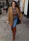 Kelly Brook looks fall festive in a tan overcoat over a sweater and knee high boots at Heart radio in London, UK
