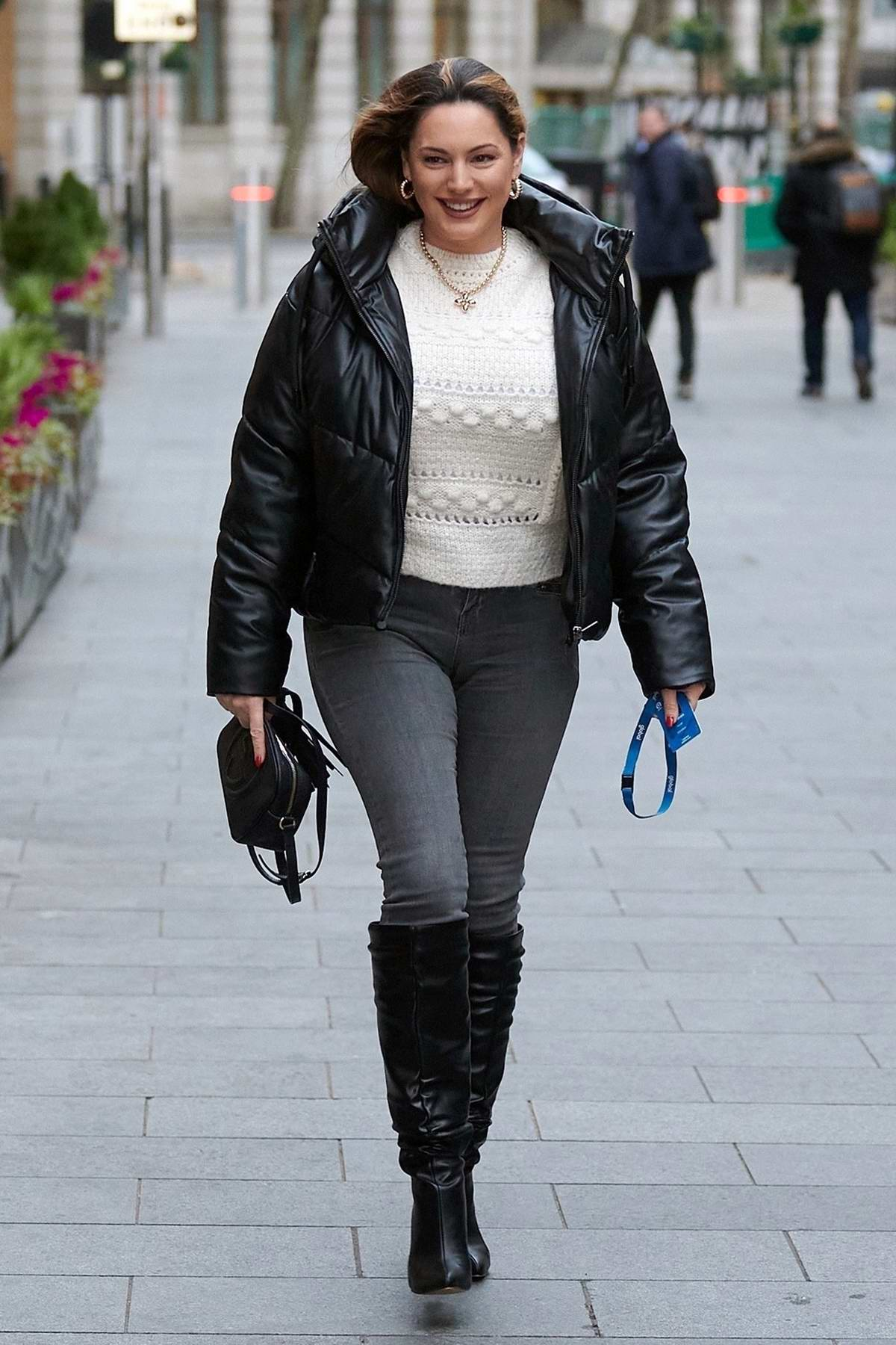 Kelly Brook rocks a black puffy jacket with tight jeans and knee-high boots as she arrives at Heart radio in London, UK