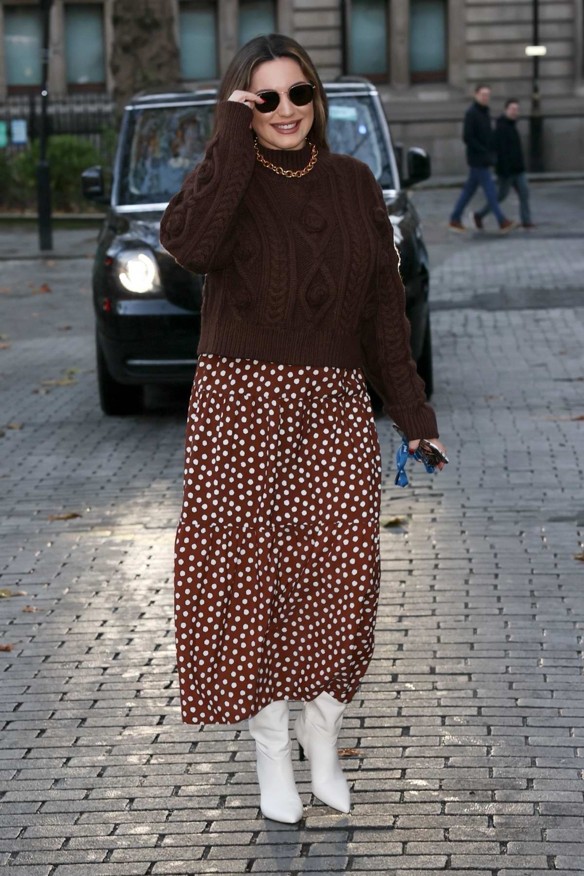 Kelly Brook wears a polka dot skirt and a brown sweater as she arrives at the Heart Radio Studios in London, UK