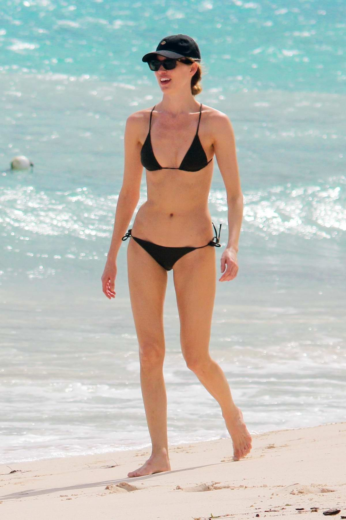 Martha Hunt stuns in a black bikini while enjoying a stroll through the beach with fiancé Jason McDonald in Tulum, Mexico