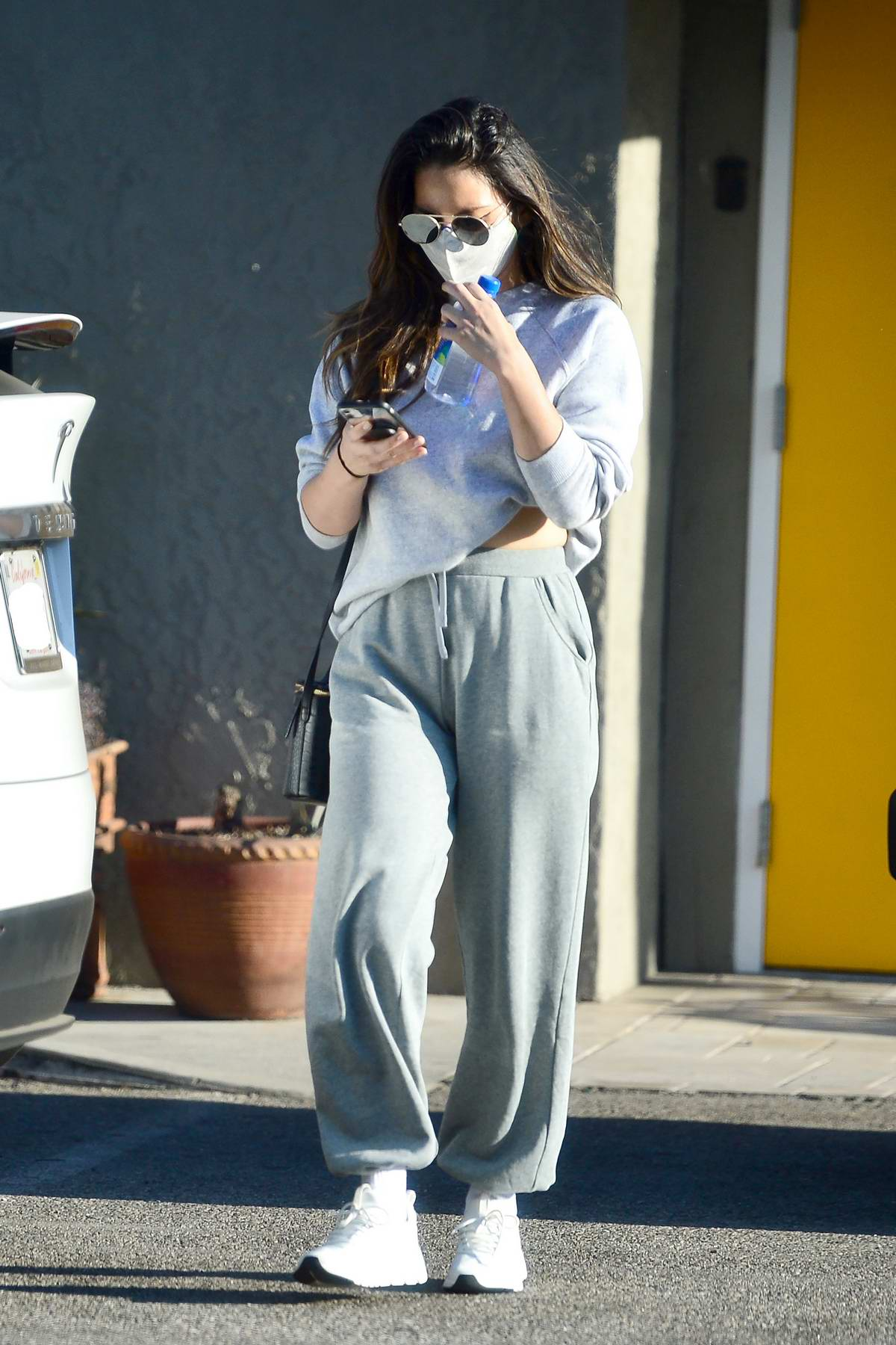 Olivia Munn looked busy on her phone as she leaves the gym after a workout in Los Angeles