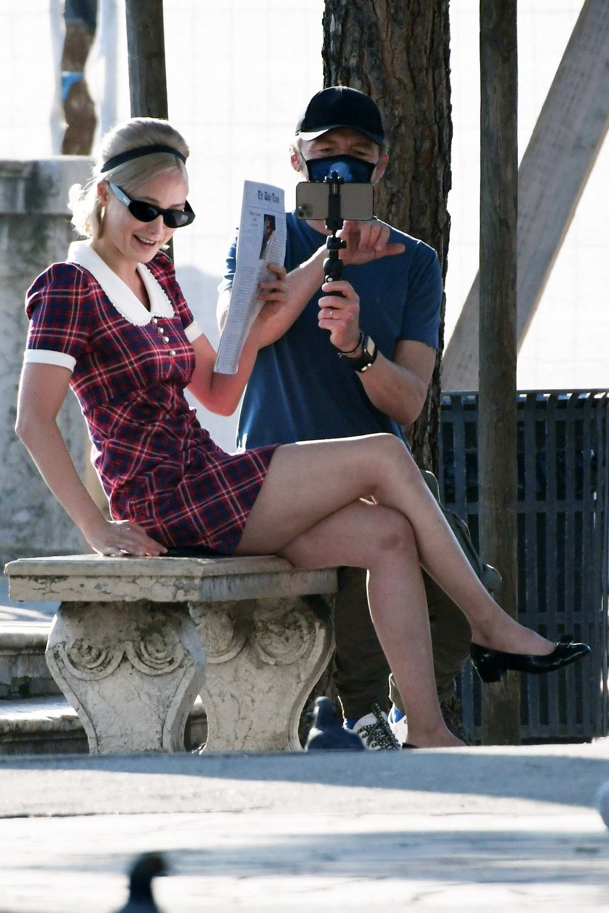 Pom Klementieff poses in a plaid minidress while Simon Pegg filming her on a mobile phone in Venice, Italy