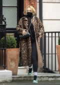 Rita Ora bundles up in a leopard print coat over a black hoodie and leggings as she steps out in central London, UK