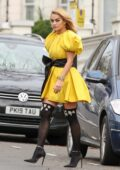 Rita Ora puts on a stunning display as she steps out in a bright yellow dress in London, UK