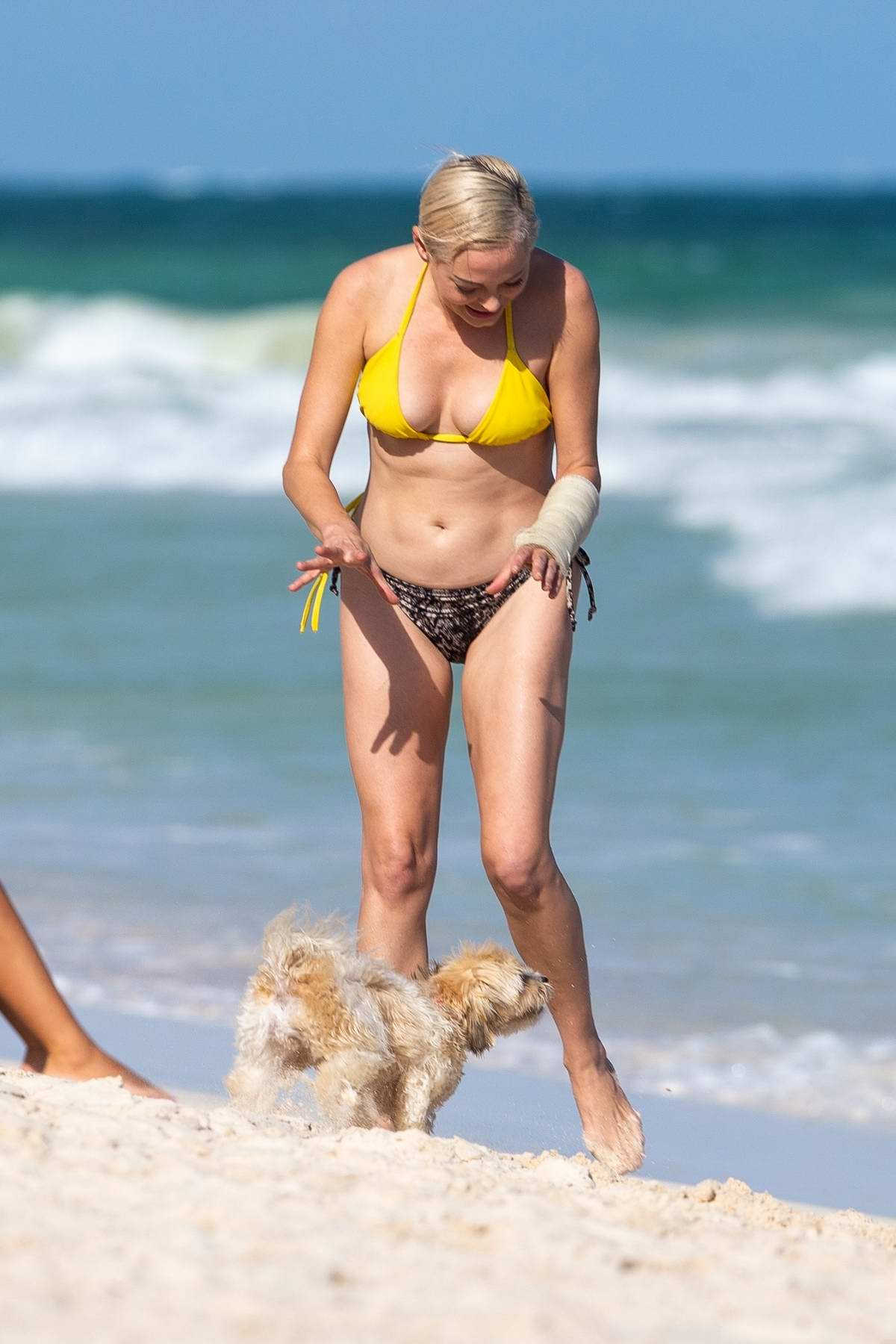 Rose McGowan seen wearing a yellow bikini while playing with her pup at the beach in Tulum, Mexico
