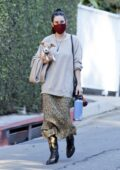 Scout Willis wears a beige sweater with a floral print skirt and cowgirl boots while out with her pup in Los Feliz, California
