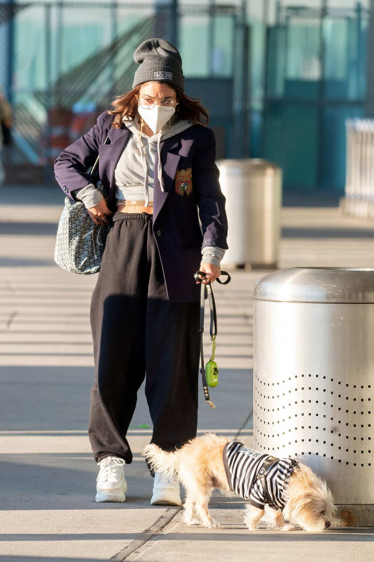 Vanessa Hudgens stays warm in a hoodie and blazer as she arrives with her dog for a flight out of JFK Airport in New York