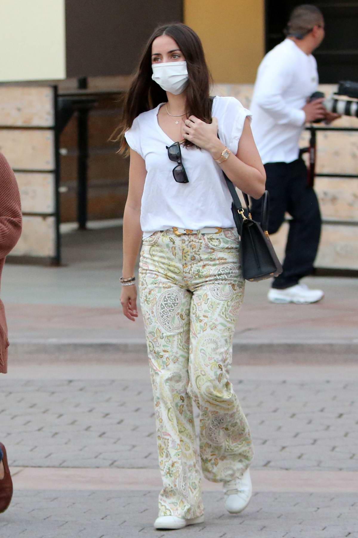 Ana de Armas dons a white top and paisley print denim while shopping for Christmas presents in Santa Monica, California