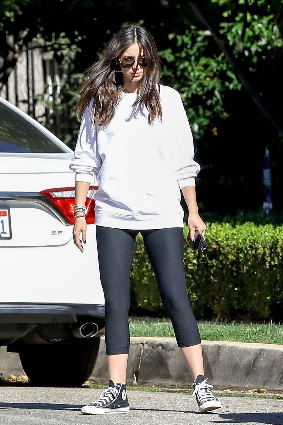 Ana de Armas sports a white sweatshirt with black leggings for a stroll with friends in Brentwood, California