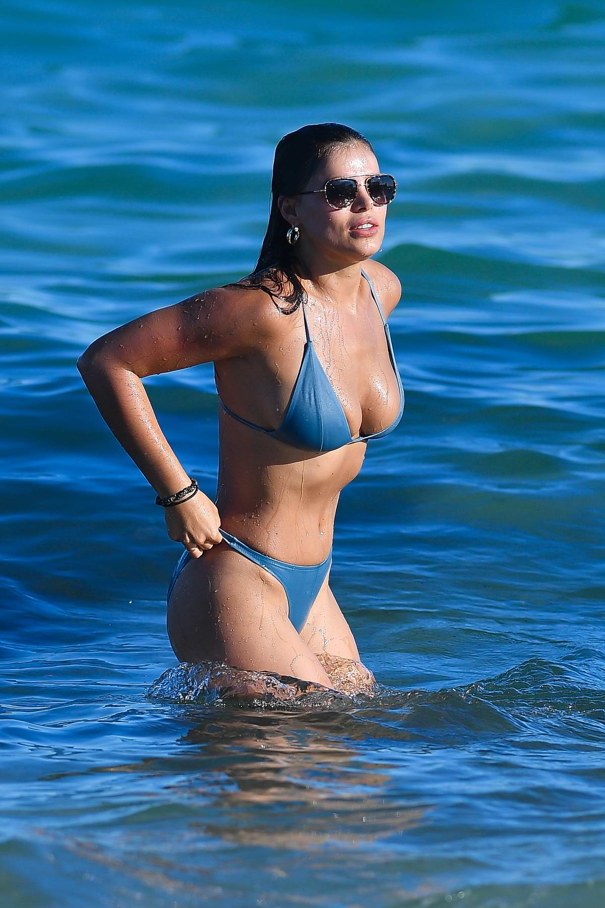 Brooks Nader shows off her beach body in a blue bikini as she hits the beach with Billy Haire in Miami, Florida