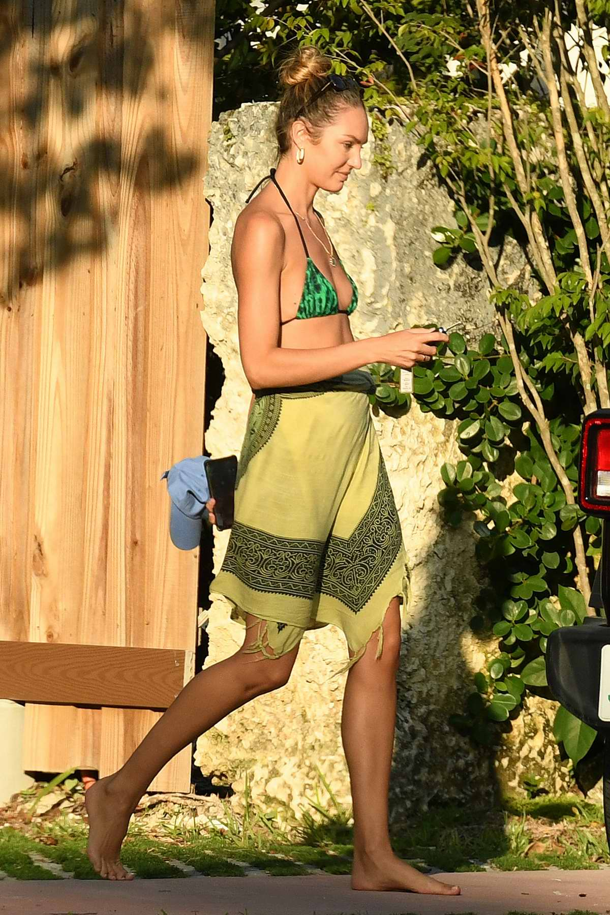 Candice Swanepoel wears a green bikini top with a sarong while out around her neighborhood in Miami Beach, Florida
