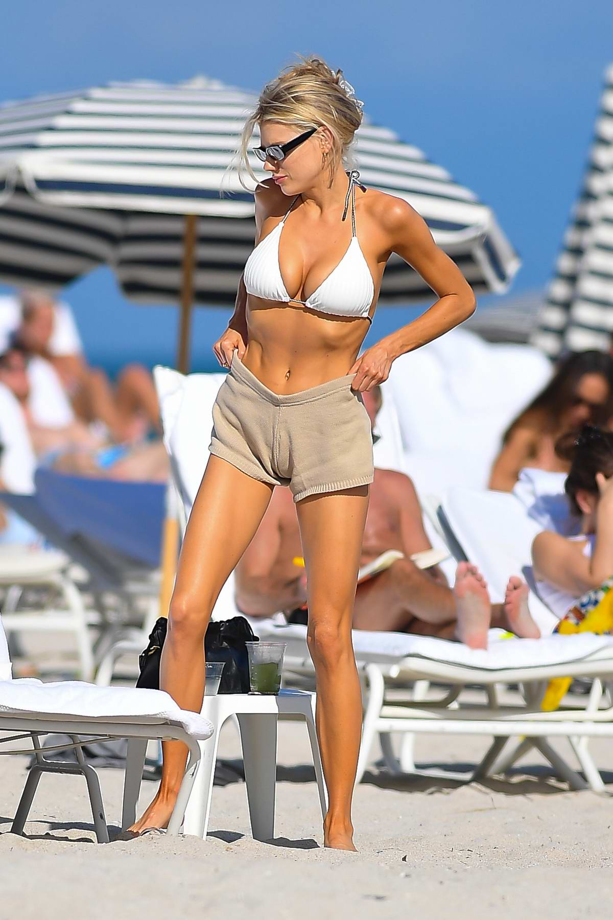 Charlotte McKinney shows off her beach body in a white bikini top and shorts while enjoying a beach day in Miami, Florida