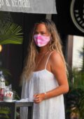 Chrissy Teigen enjoys a cold drink with friends in Gustavia during her holiday break in St Barts, France