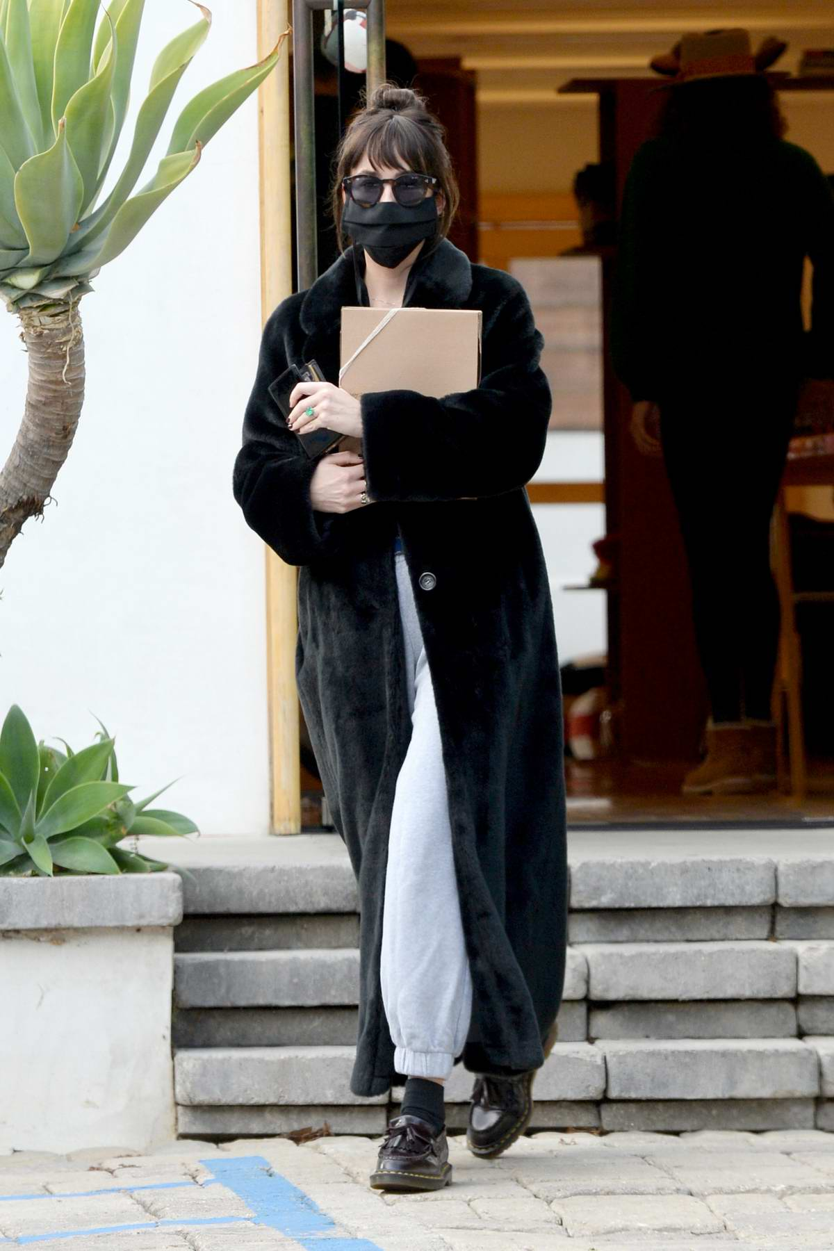 Dakota Johnson looks cozy in a black long coat while shopping at The Elder Statesman in West Hollywood, California