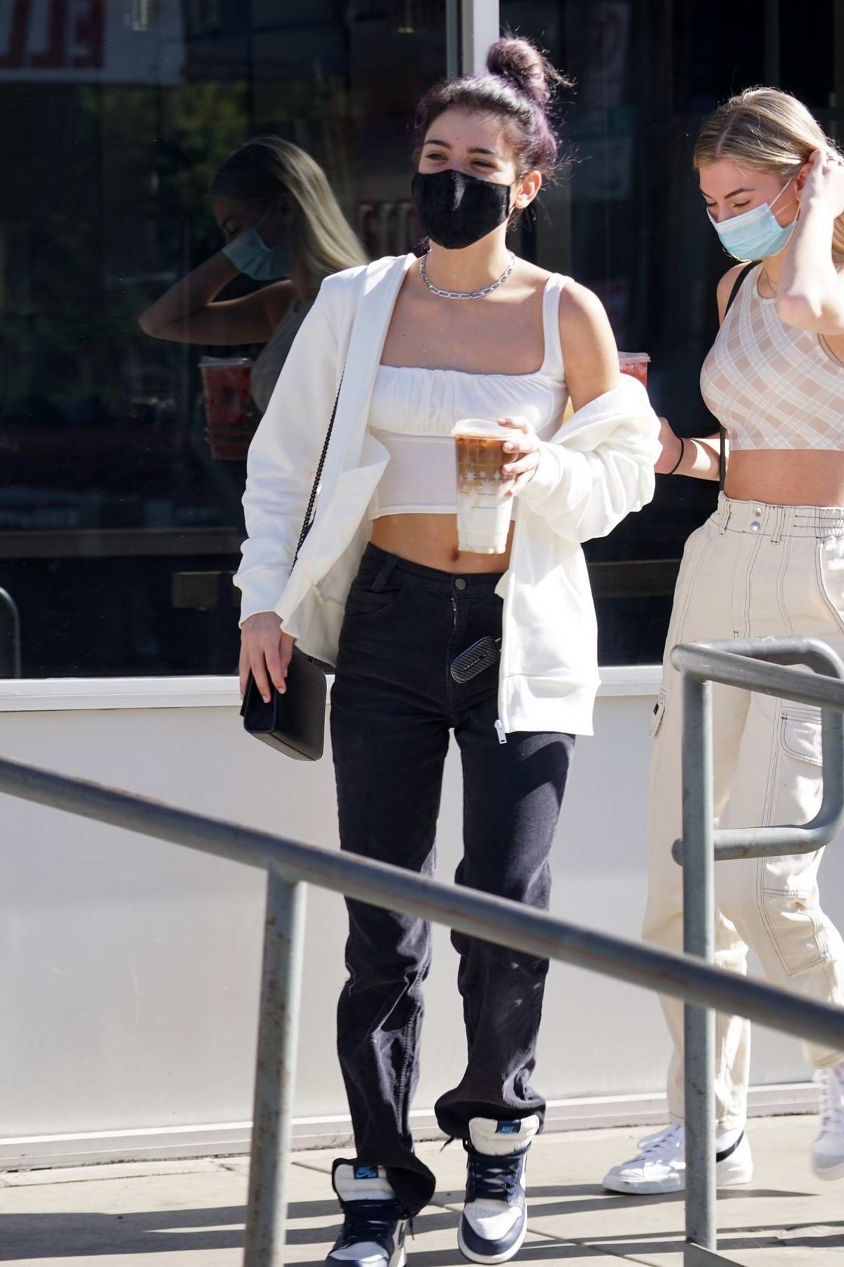 Dixie D'Amelio flashes her midriff while out for coffee with a friend in West Hollywood, California