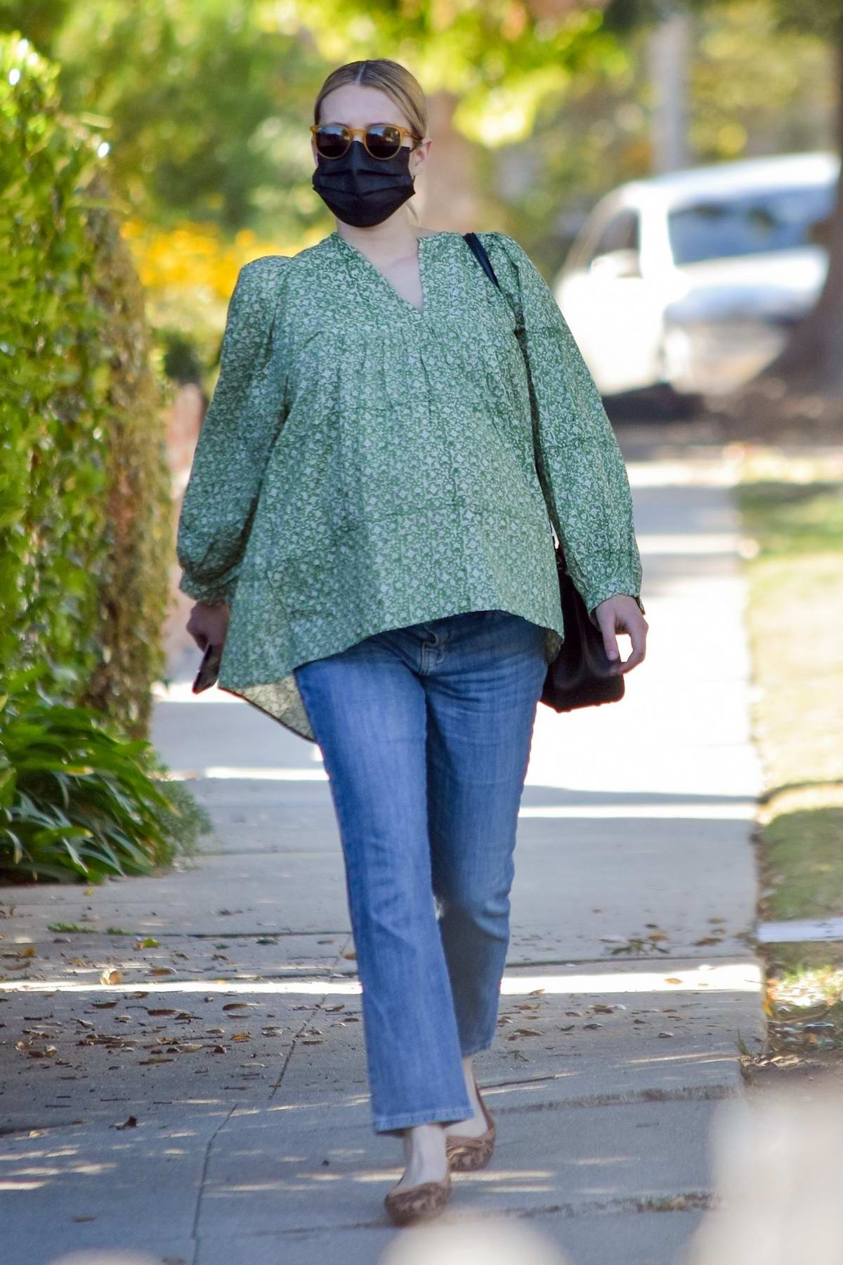 Emma Roberts conceals her growing belly in a patterned green top as she goes holiday shopping at Buck Mason in Los Angeles