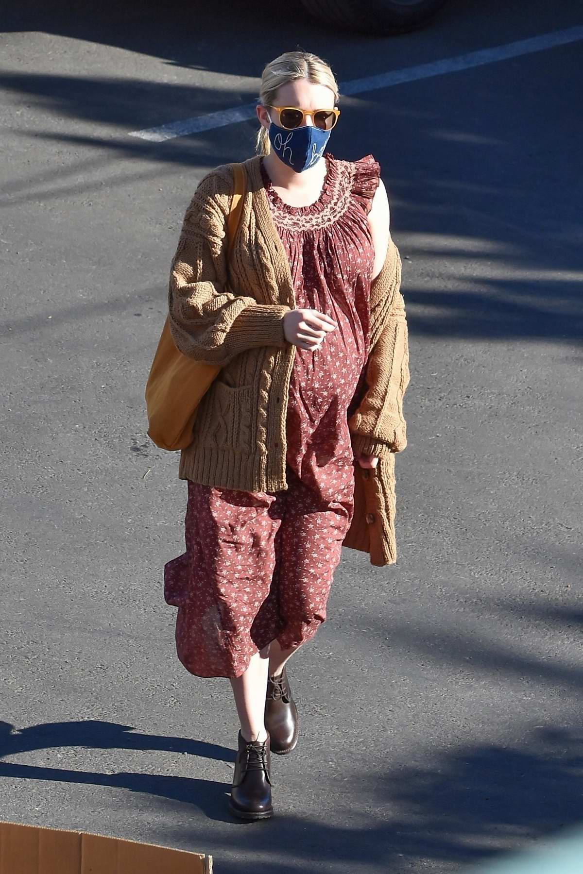 Emma Roberts dons a cute patterned dress with a brown cardigan on top while out running errands in Los Angeles