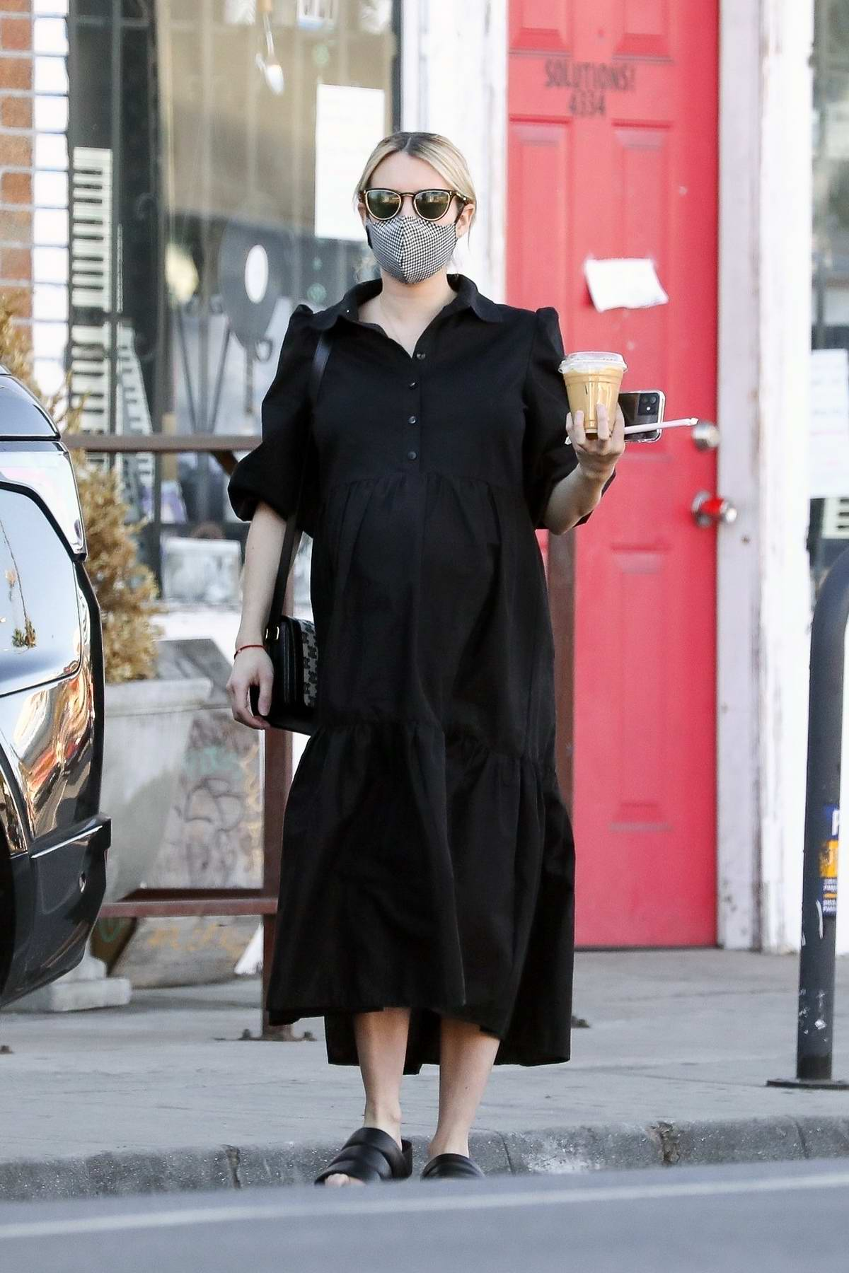 Emma Roberts wears a black dress while picking up some coffee to go while out running errands in Los Angeles