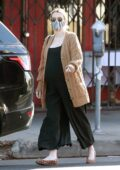 Emma Roberts wears a black jumpsuit with a brown cardigan during a solo coffee run in Los Feliz, California