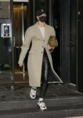 Hailey Bieber looks stylish in a beige trench coat and black leather pants as she heads out of her apartment in New York City