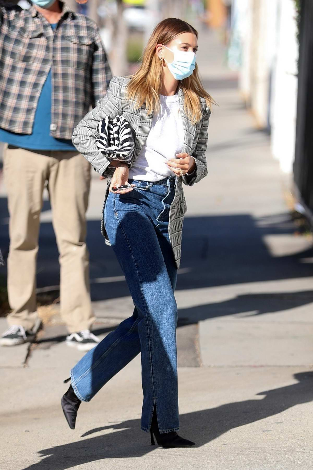 Hailey Bieber seen wearing a grey blazer and jeans as she arrives at a film set in West Hollywood, California