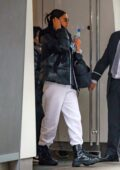 Irina Shayk wears a black puffer jacket over white sweats as she heads out of her apartment to run errands in New York City