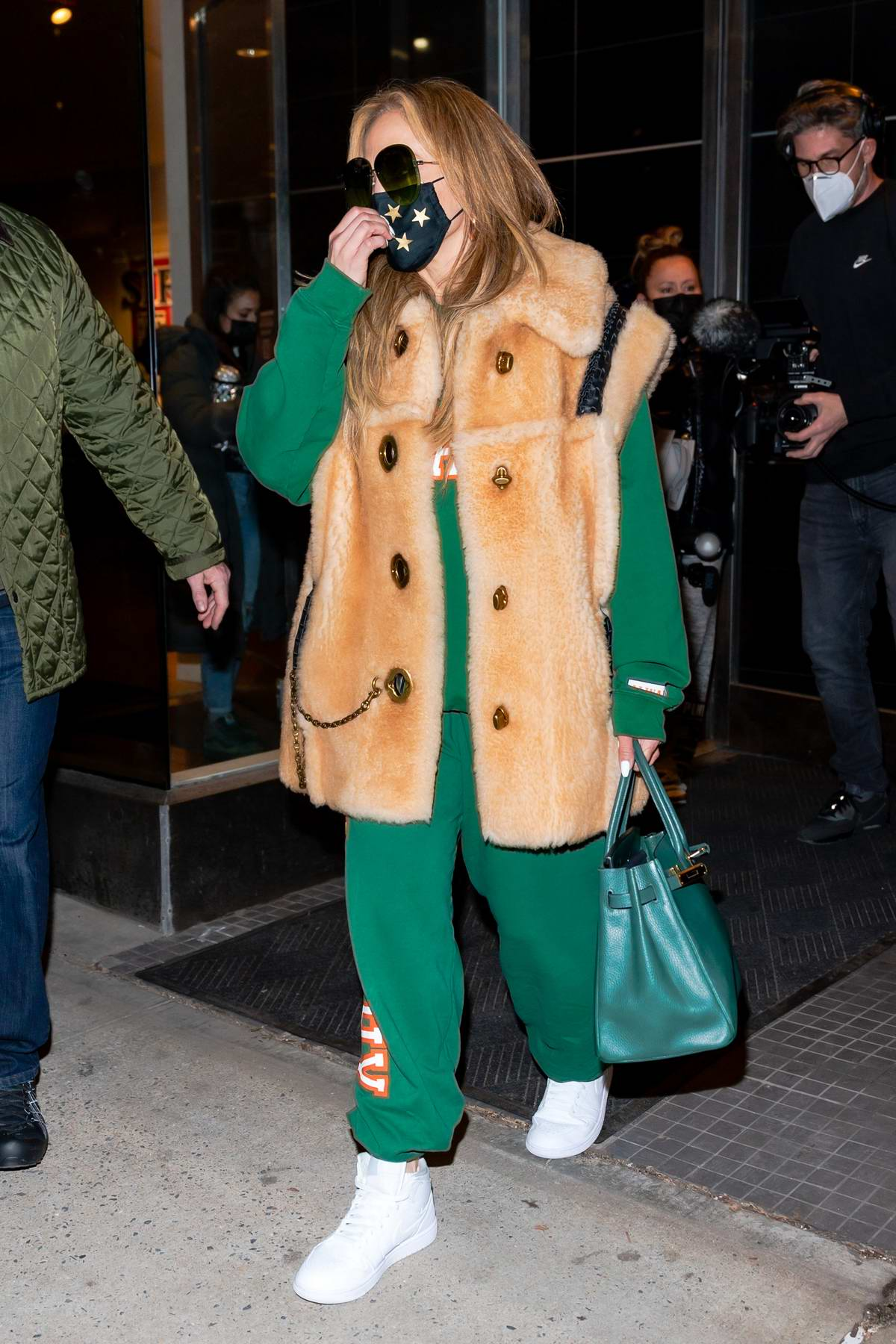Jennifer Lopez wears a fur vest over her green sweatsuit as she heads out after rehearsals in New York City