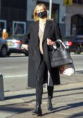 Karlie Kloss covers her baby bump under black trench coat while stepping out in SoHo, New York
