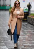 Kelly Brook wears a beige coat with a matching sweater as she arrives at Heart radio in London, UK