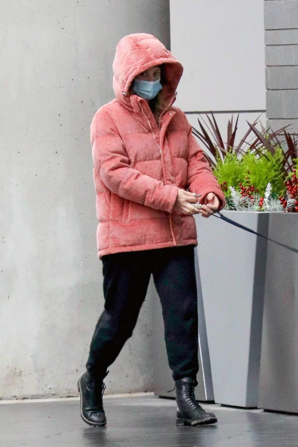 Lili Reinhart dresses in a hooded puffer jacket while for a walk with her dog Milo in Vancouver, Canada