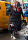 Martha Hunt bundles up in a long puffer coat as she returns to her hotel after a photoshoot in New York City