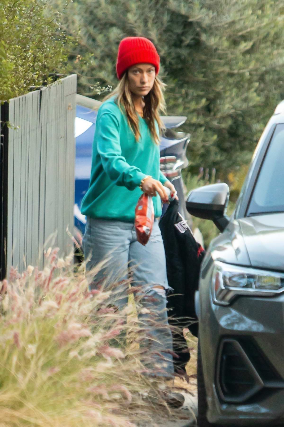 Olivia Wilde picks up some stuff as she leaves her house in Los Angeles