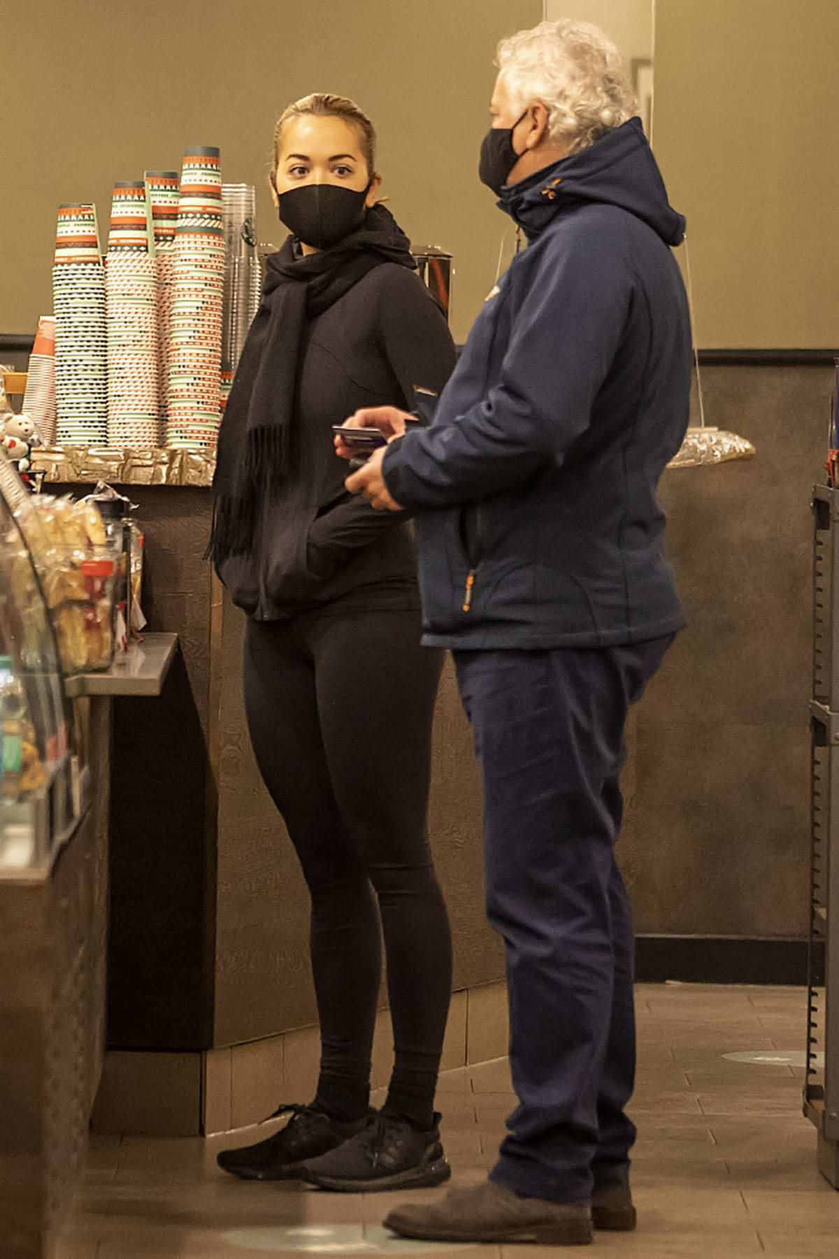 Rita Ora sports all-black activewear while out with her father for some coffee in Kensington, London, UK