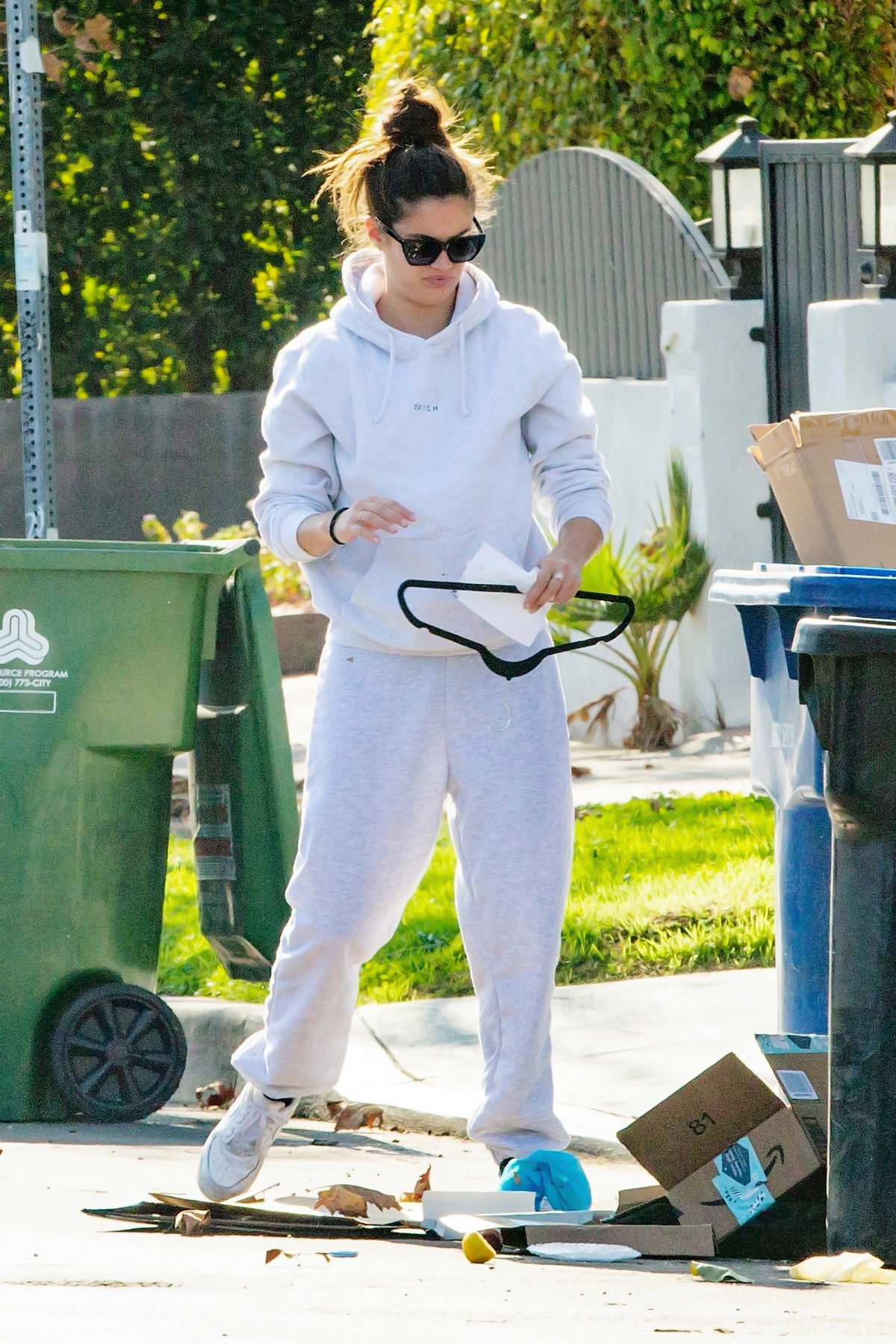 Sara Sampaio seen cleaning up a mess that the trash-men left outside her home in Los Angeles
