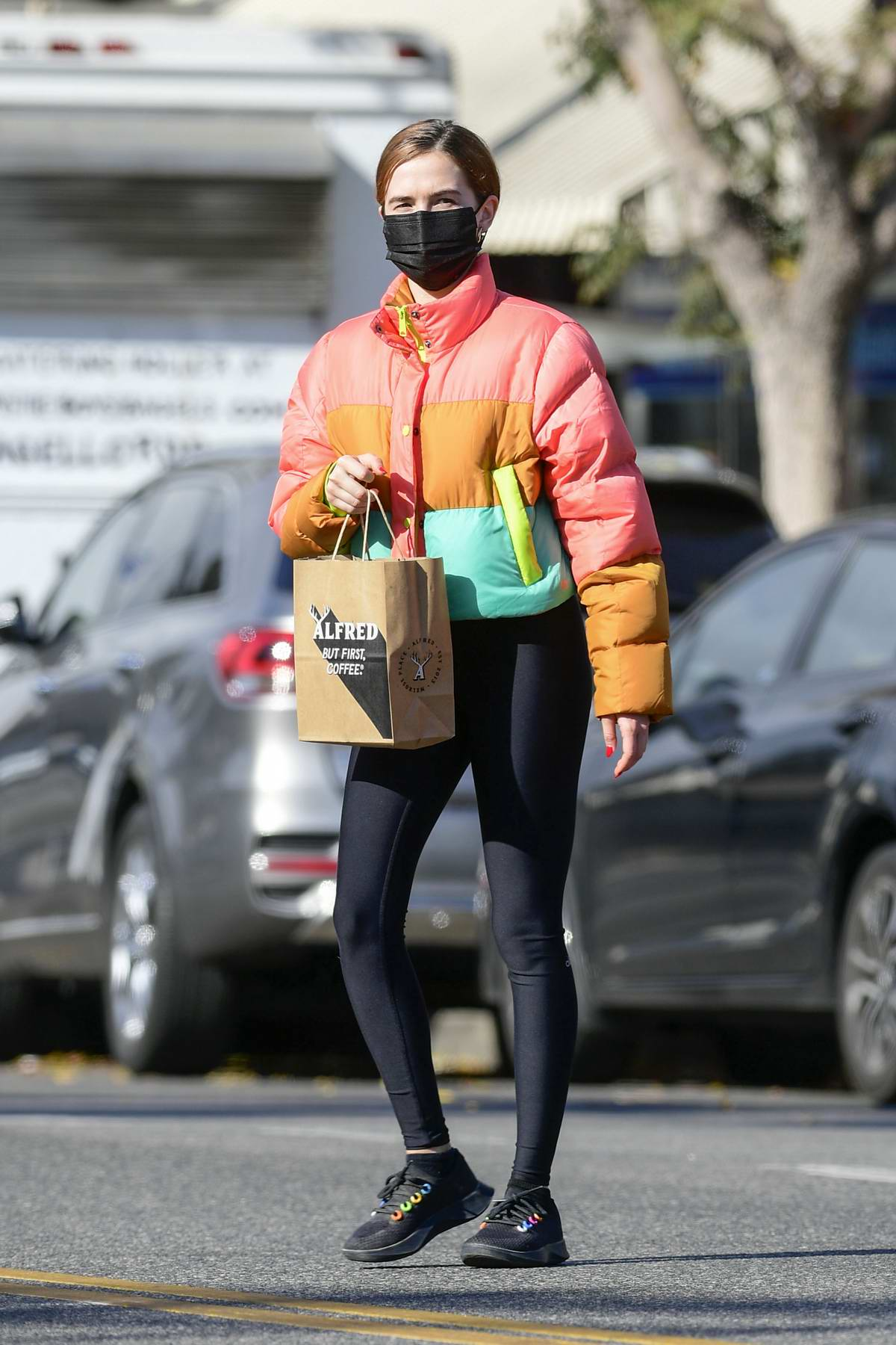 Zoey Deutch bundles up in a colorful puffer jacket and black leggings while making a coffee run in Los Angeles