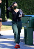 Addison Rae looks comfy in a black top, green sweatpants and red fuzzy UGG slippers as she leaves a Pilates class in Los Angeles