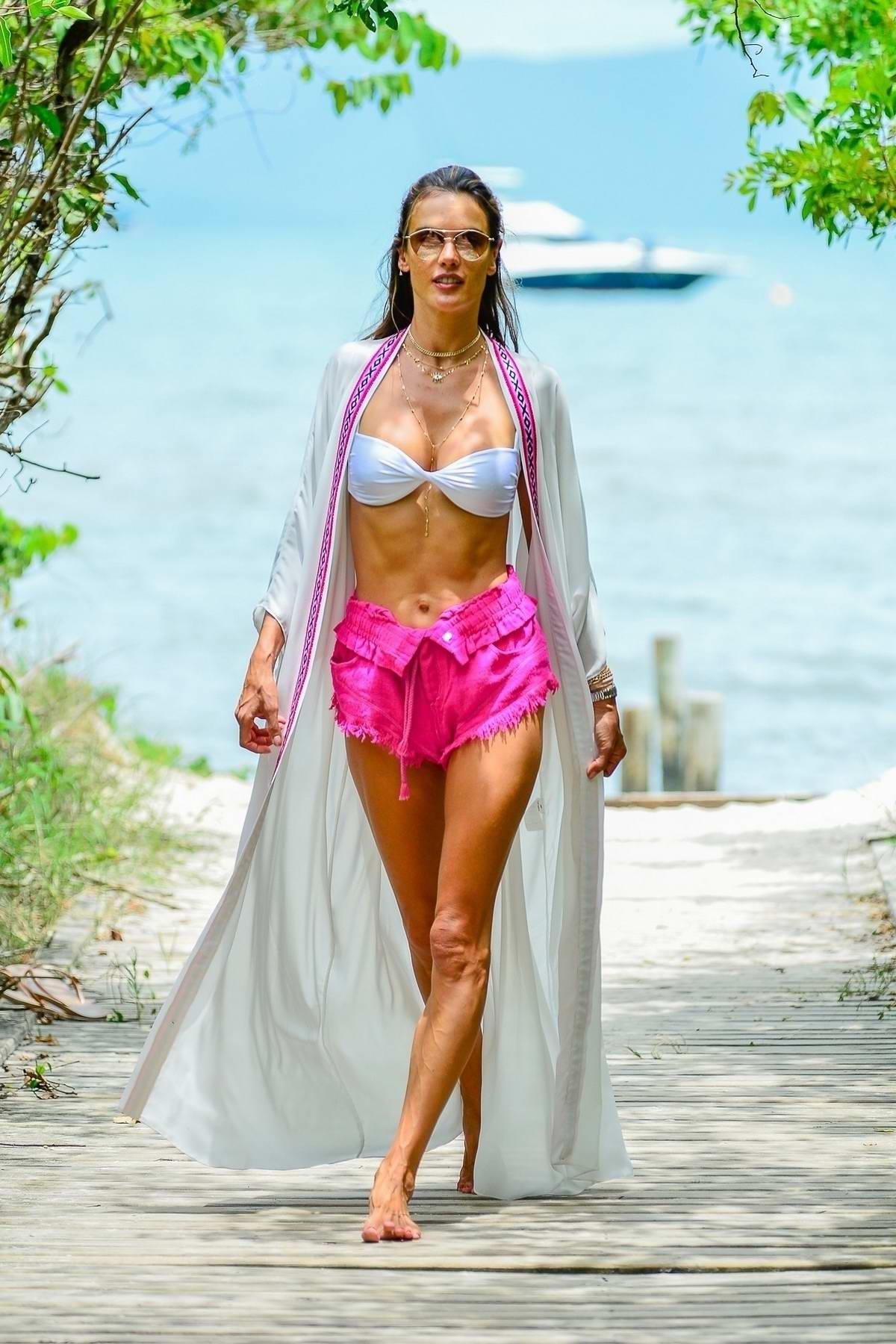 Alessandra Ambrosio flashes her midriff in bikini top and pink denim shorts as she heads for a Jet Ski ride in Florianopolis, Brazil