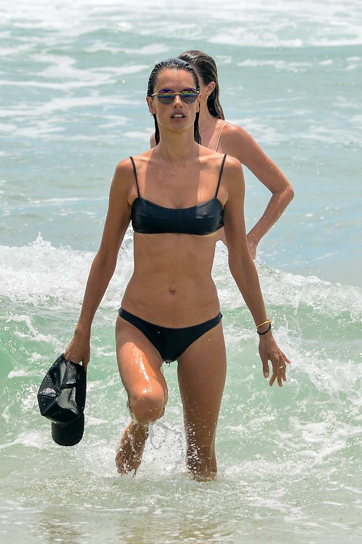 Alessandra Ambrosio shows off her toned physique in a black bikini as she gets in a beach workout in Florianopolis, Brazil