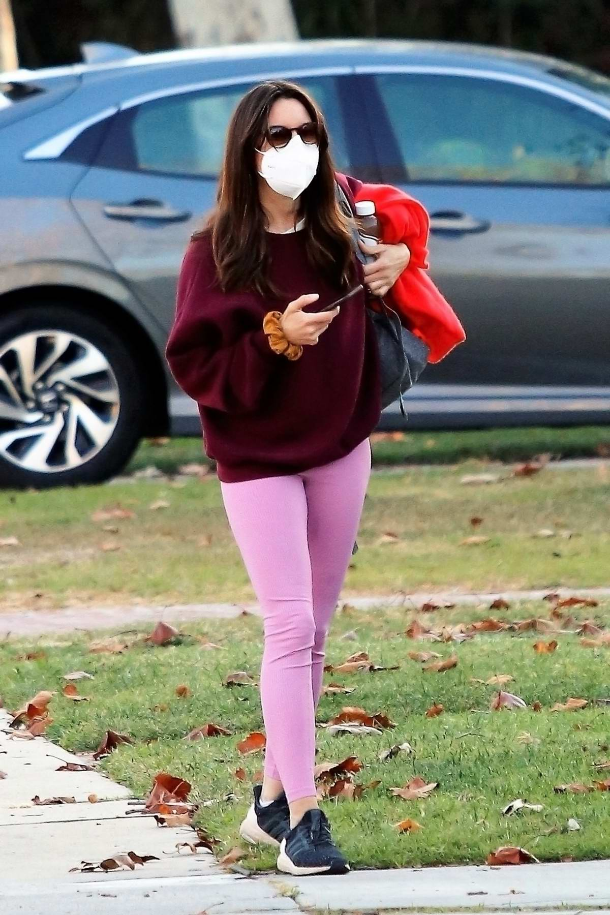 Aubrey Plaza steps out wearing a burgundy sweatshirt and bright pink leggings in Los Angeles