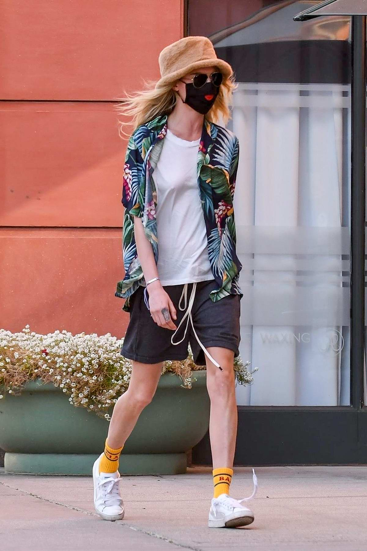 Cara Delevingne rocks a tropical print shirt, white tee and drawstring shorts as she steps out in Beverly Hills, California